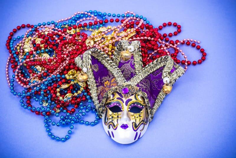 FestivalMardi Gras maskering och mångfärgade pärlor på ljus bakgrund royaltyfri bild