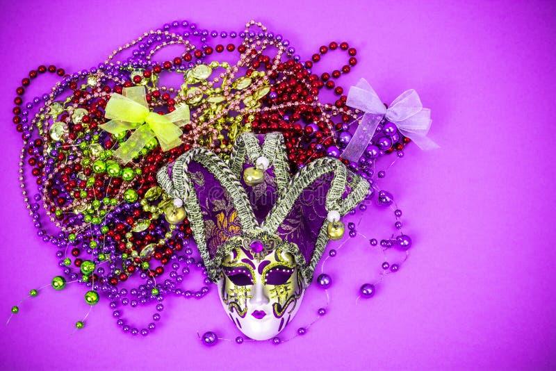 FestivalMardi Gras maskering och mångfärgade pärlor på ljus bakgrund royaltyfri fotografi