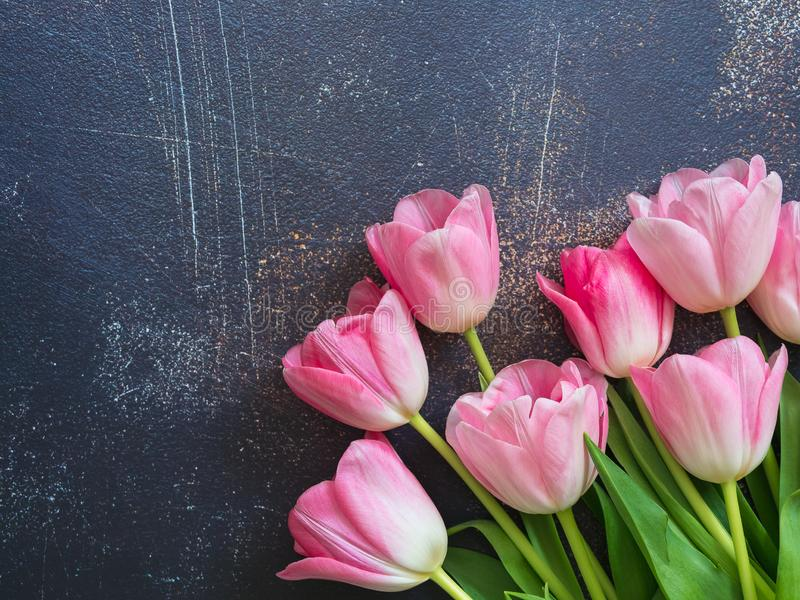 Festive background with bouquet of pink tulips on gray concrete, copy space. Backdrop for cards, invitations and greetings.  stock photo