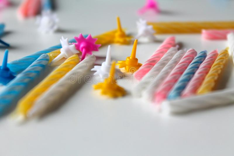 Festive background with bright colorful birthday candles on white background. Festive bright colorful birthday candles scattered on white background. Yellow royalty free stock photo
