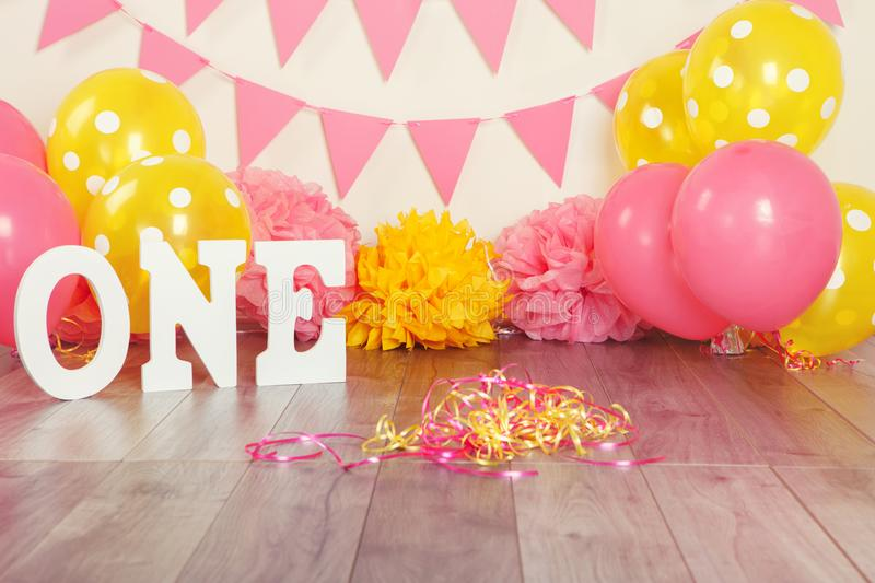 Festive background decoration for birthday celebration with letters saying one and pink red yellow balloons stock photography