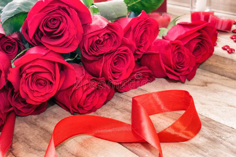 Festive background for March 8, World Women`s Day. Red roses and a red ribbon in the form of the figure eight, on a wooden backgro royalty free stock photo