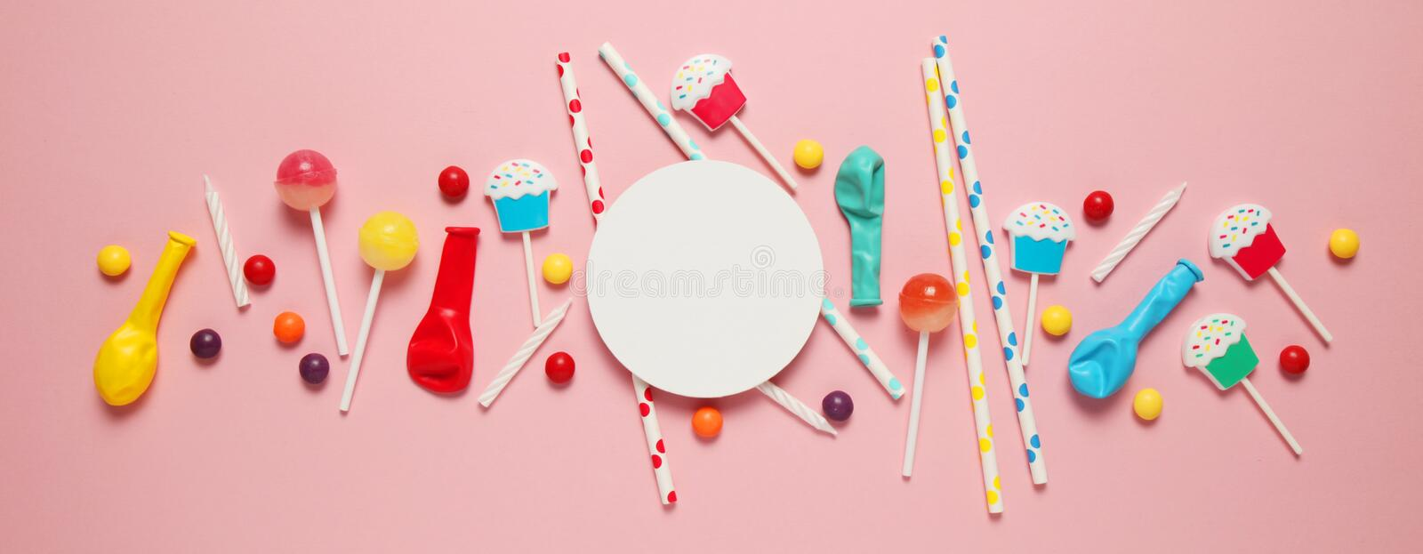 Festive background pattern of children`s holiday. Cheerful birthday party with sweets on pink background stock photo