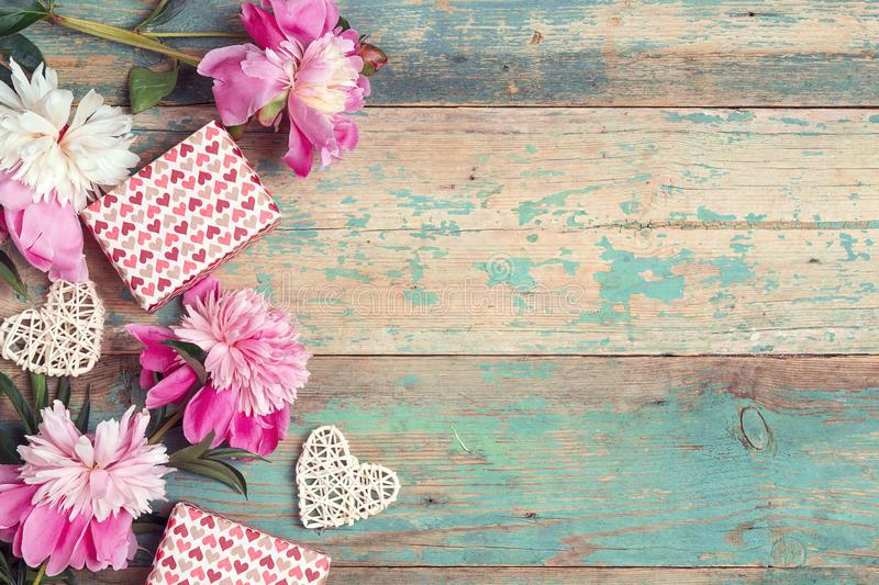 Festive background with pink peonies, gifts and hearts on an old turquoise table with shabby paint. Place for text royalty free stock photography