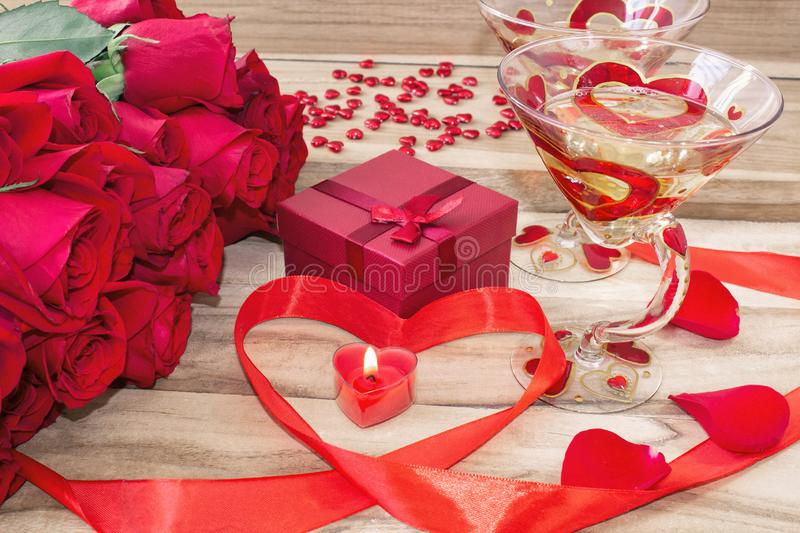 Festive background to the Valentine`s day. A bouquet of red roses, a gift box, a heart-shaped candle and a red ribbon with a heart royalty free stock photos