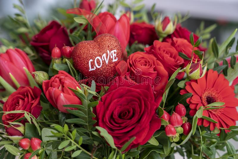 A festive bouquet of a variety of red flowers and a heart with the inscription love for Valentine`s day and other holidays.  royalty free stock photos