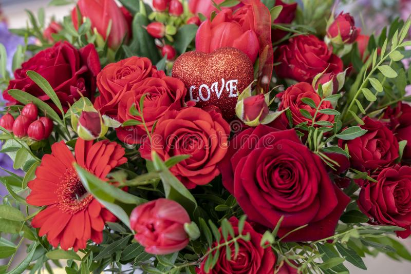 A festive bouquet of a variety of red flowers and a heart with the inscription love for Valentine`s day and other holidays.  stock photo