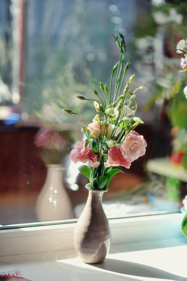 Festive bouquet. On the window sill is a bouquet of pink roses in a beautiful decorative vase stock image