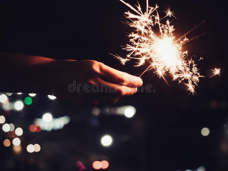Festive, bright, burning Bengal lights in the man`s hand royalty free stock images