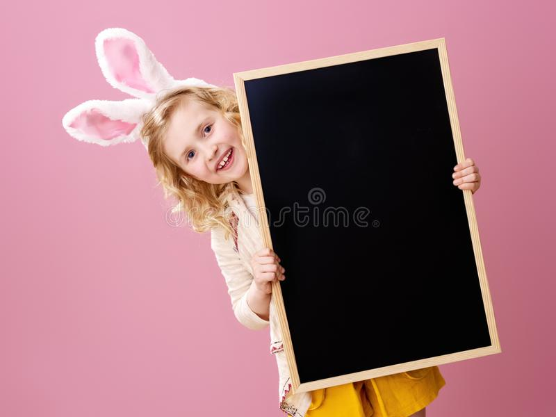 Happy modern girl isolated on pink looking out from blank board royalty free stock photography