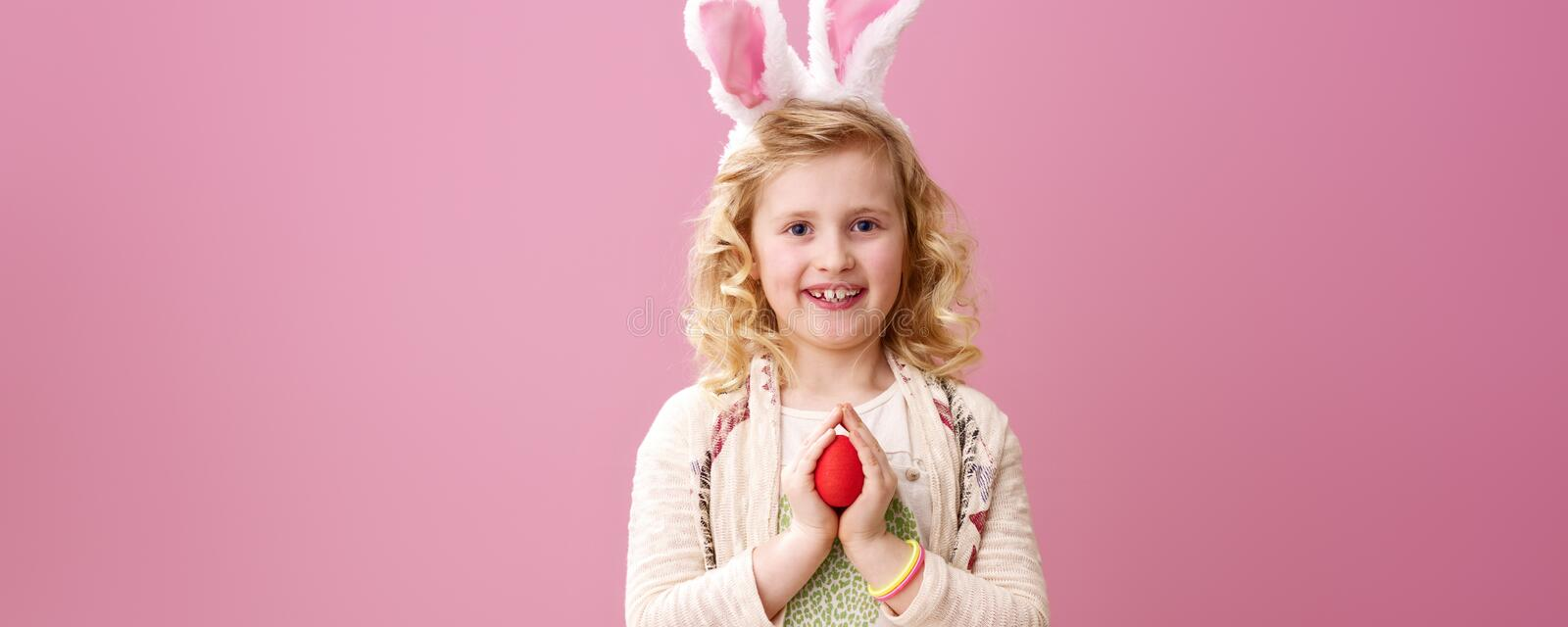 Happy stylish child on pink background with red Easter egg stock photos