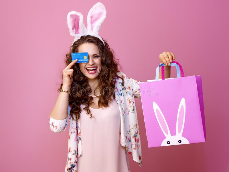 Woman on pink with Easter shopping bag and credit card royalty free stock image