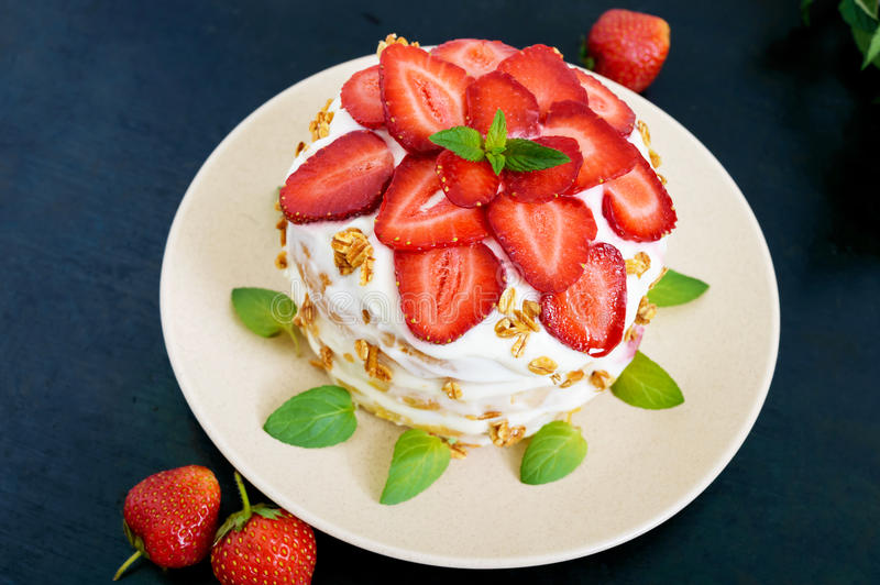 A festive cake with fresh strawberries, cream, decorated with mint leaves stock photo