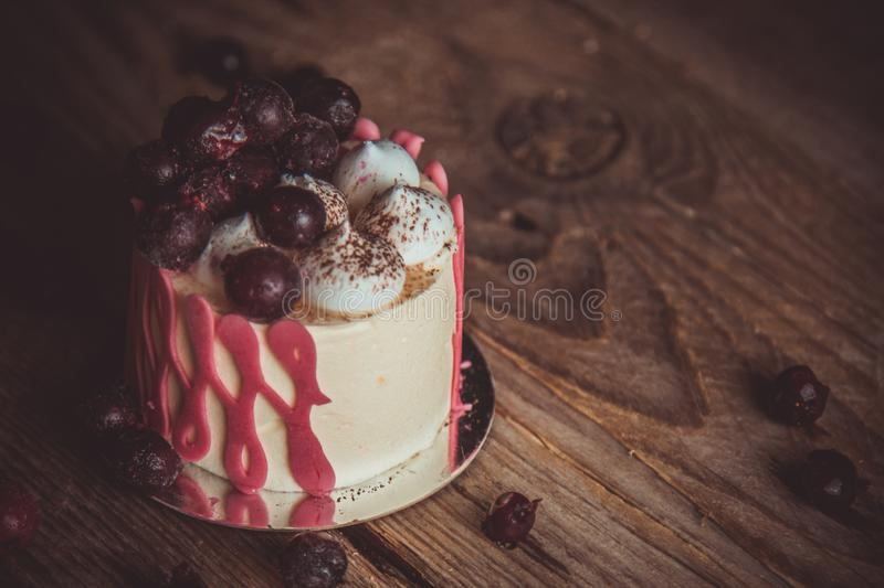 Festive cake with the fruits of cherry on a rustic wooden table on a dark background. close up copy space. vintage pattern on royalty free stock image