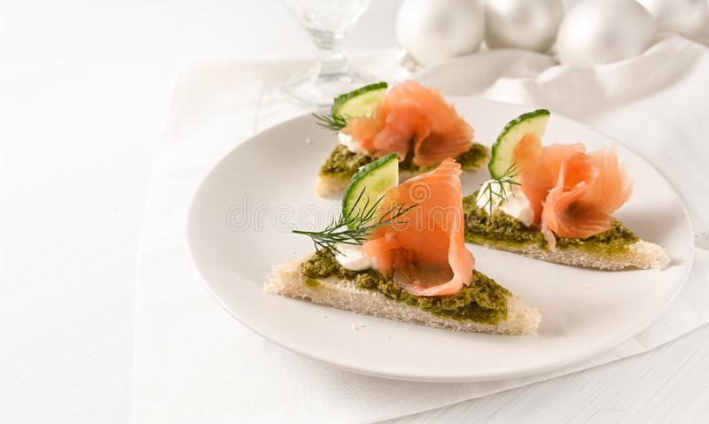 Festive canapes with smoked salmon on a plate on a white table with christmas decoration, large copy space. Selected focus, narrow depth of field stock images