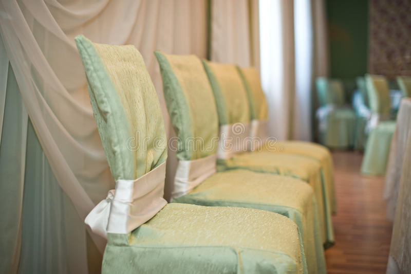 Festive chairs. Decorated with a gentle and green and pink fabric chairs in a festive hall royalty free stock images