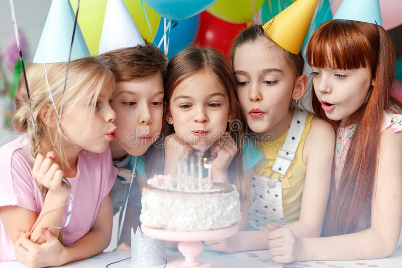Festive children in party caps, blow candles on delicious cake, make wish, celebrate birthday, have party together, hold stock images