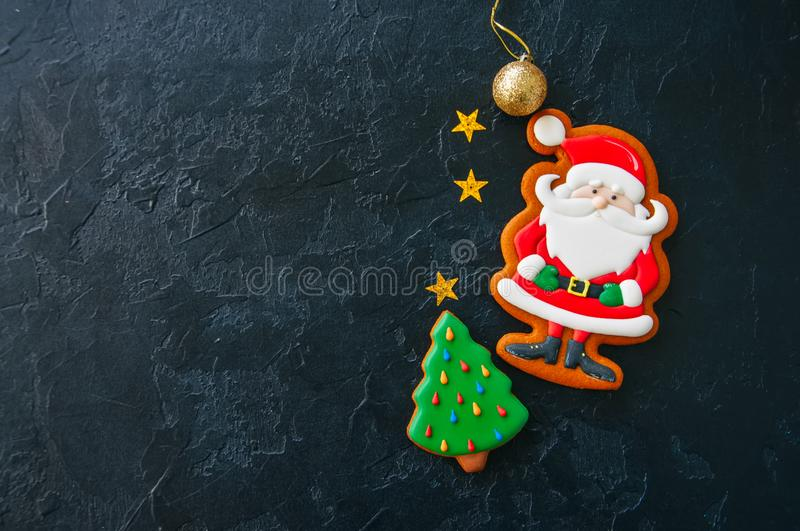 Festive Christmas background, Cookies with image of Santa, fir t. Ree, stars and ball on a black stone background. Top view with copy space stock photo