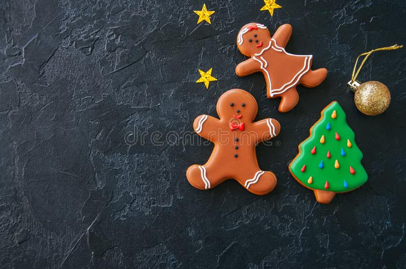 Festive Christmas background, Cookies with images of Gingerbread. Man and girl fir tree, stars and ball on a black stone background. Top view with copy space stock images
