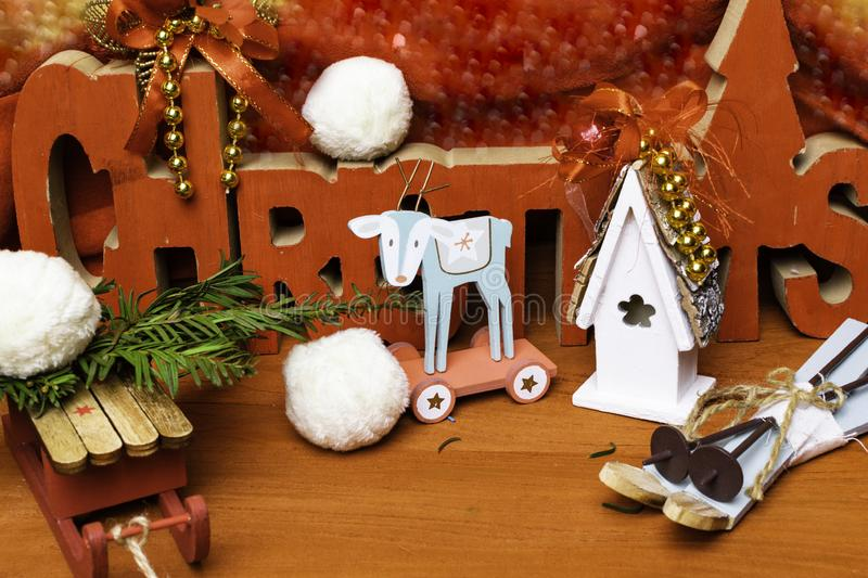 Festive christmas background with toy deer, house, sledge, ski and snow. Festive christmas wooden background with toy deer, house, sledge, ski and snow, and text stock photography