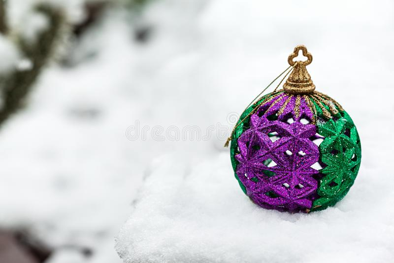 Festive Christmas ball colored in green and purple in the winter day on a white snow with copy space on the left. Image stock images