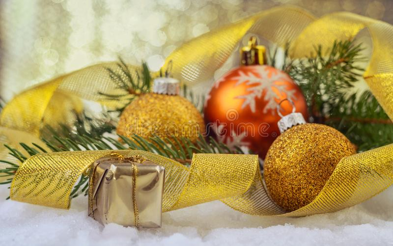 Festive Christmas balls, small box with present, gold ribbon and fir branches. Christmas balls, small box with gifts, gold festive ribbon and fir branches on the stock photography