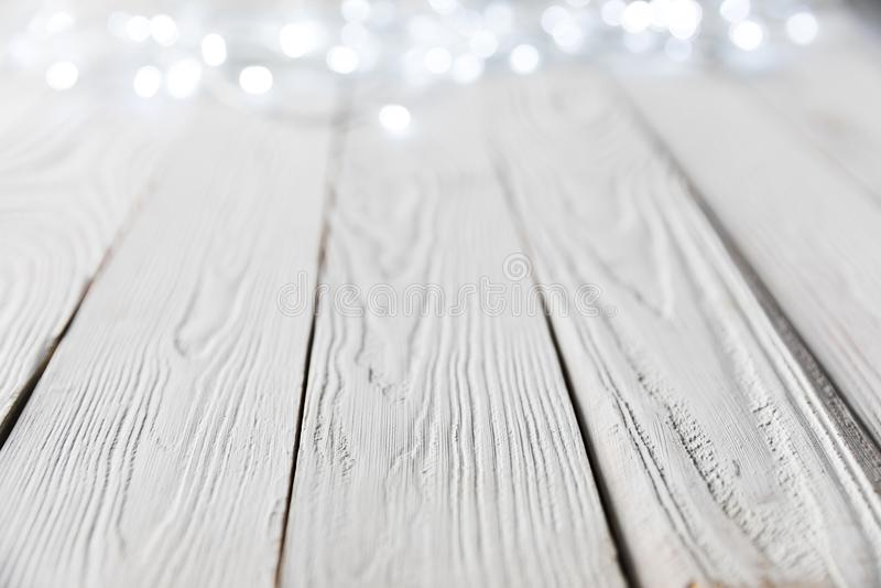 Festive christmas bokeh lights on white. Wooden surface stock photo