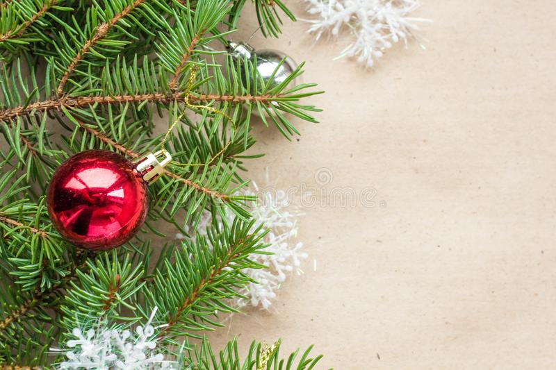 Festive christmas border with red and silver balls on fir branches and snowflakes on rustic beige background.  royalty free stock image