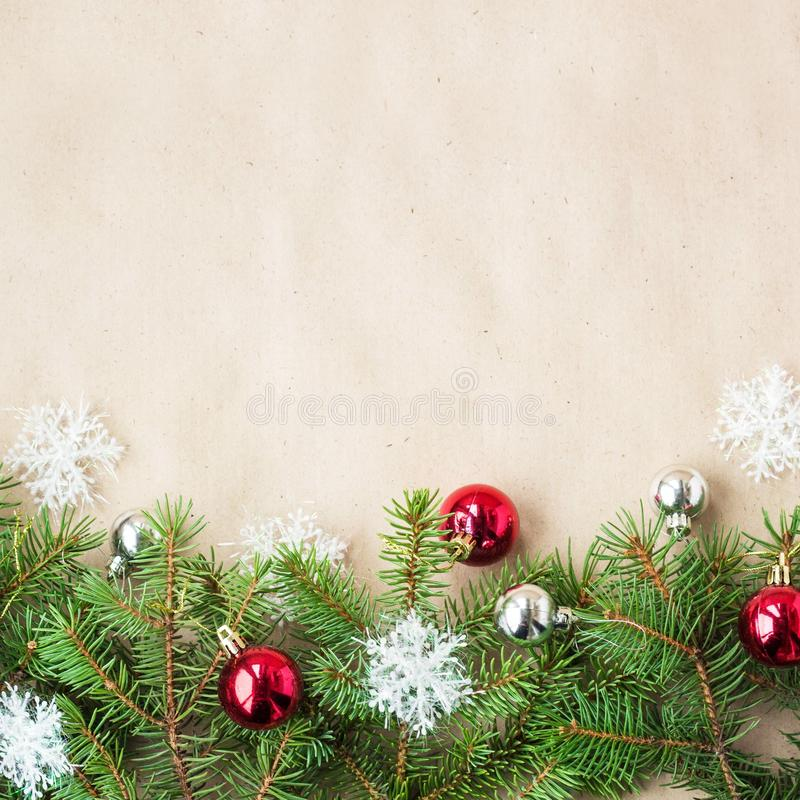 Festive christmas border with red and silver balls on fir branches and snowflakes on rustic beige background stock image