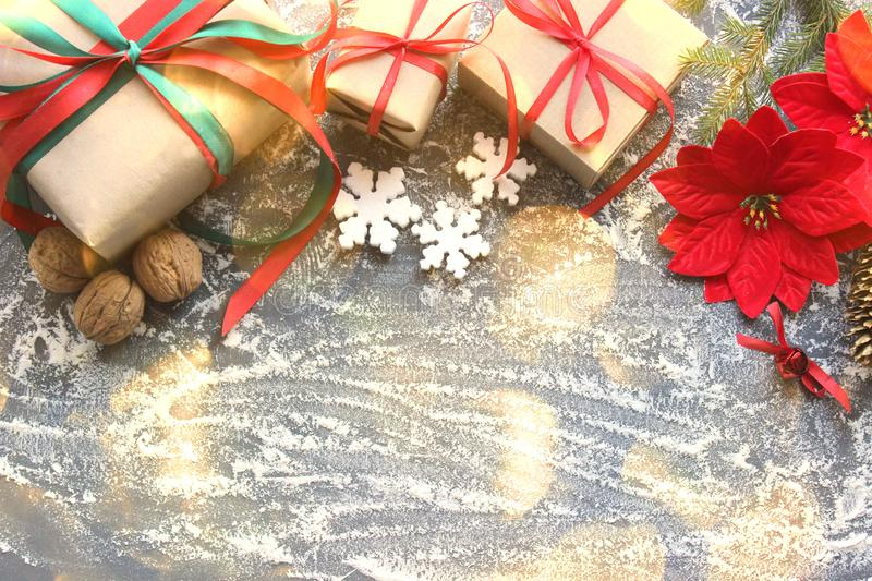 Festive Christmas composition with gifts, boxes, cones, walnuts, red flowers of poinsettia on a wooden background with white sprin. Festive Christmas composition stock photography