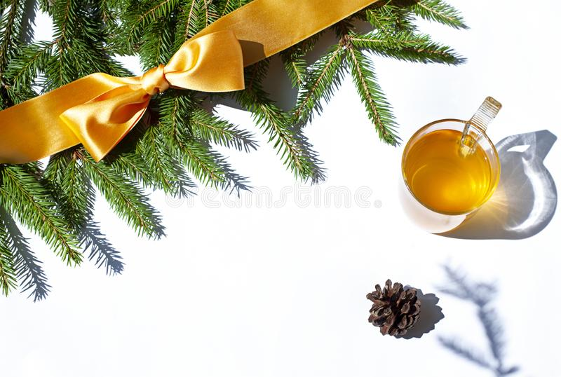 Festive Christmas concept frame with fir and a yellow bow with a cup of green tea on the white background. stock images
