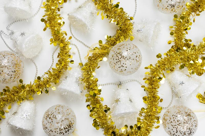 Festive Christmas decorations taking up the whole frame. Golden tinsel garland, shiny ornament balls, white and silver bells stock photo