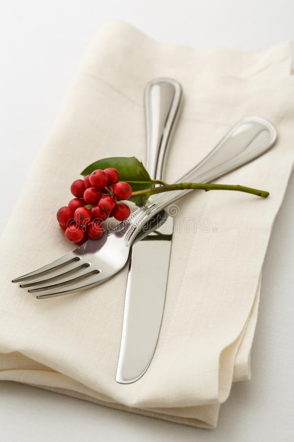 Festive Christmas dinner table setting place setting with silverware fork and knife on cloth napkin with holly berries decorations. Simple, classic Christmas royalty free stock photography