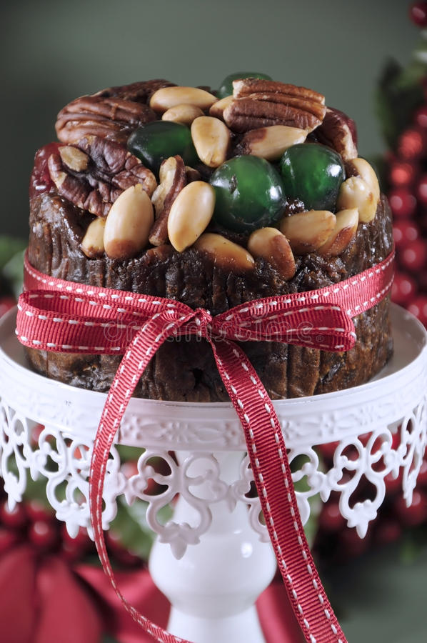 Festive Christmas food, fruit cake with glace cherries and nuts on white cake stand royalty free stock images