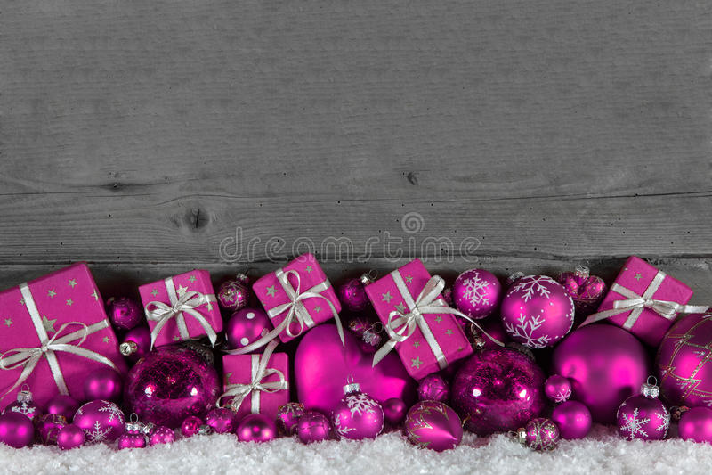 Festive christmas frame: wooden background with pink presents an. Festive christmas frame: wooden background with pink gifts and balls royalty free stock images