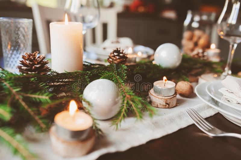 Festive Christmas and New Year table setting in scandinavian style with rustic handmade details in natural and white tones. Dining place decorated with pine royalty free stock photos