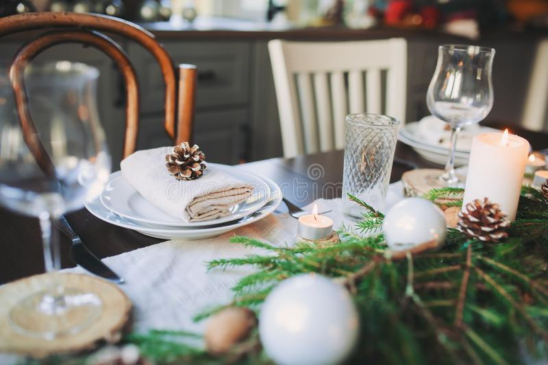 Festive Christmas and New Year table setting in scandinavian style with rustic handmade details in natural and white tones. Dining place decorated with pine stock image