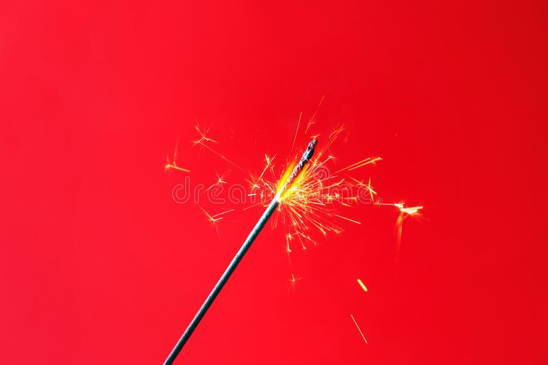 Festive Christmas sparkler on color background royalty free stock photography
