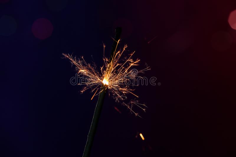 Festive Christmas sparkler on dark color background royalty free stock image