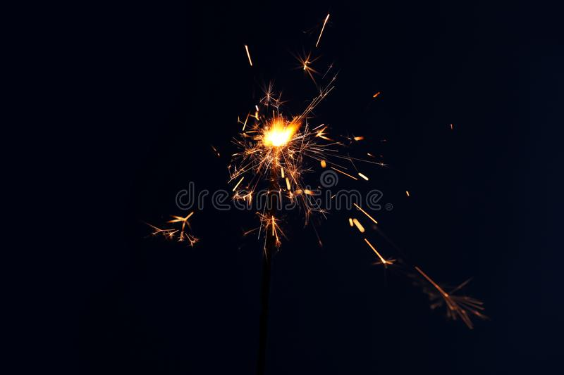 Festive Christmas sparkler on dark color background royalty free stock photos