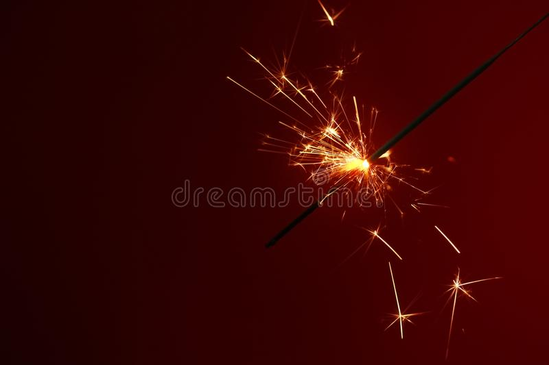 Festive Christmas sparkler on dark color background royalty free stock photography