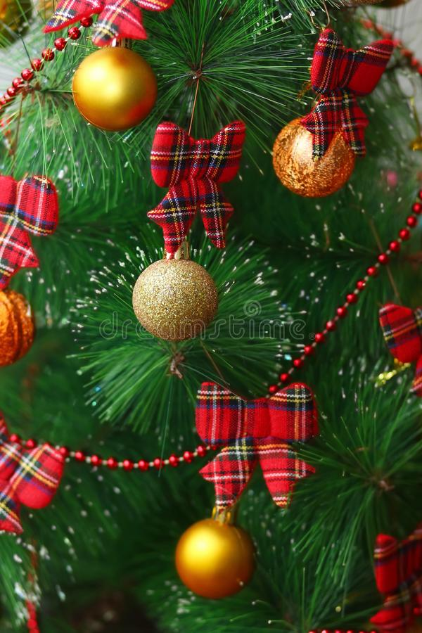 Festive close up Christmas tree vertical background with golden and glittering baubles and tartan red bows royalty free stock photo
