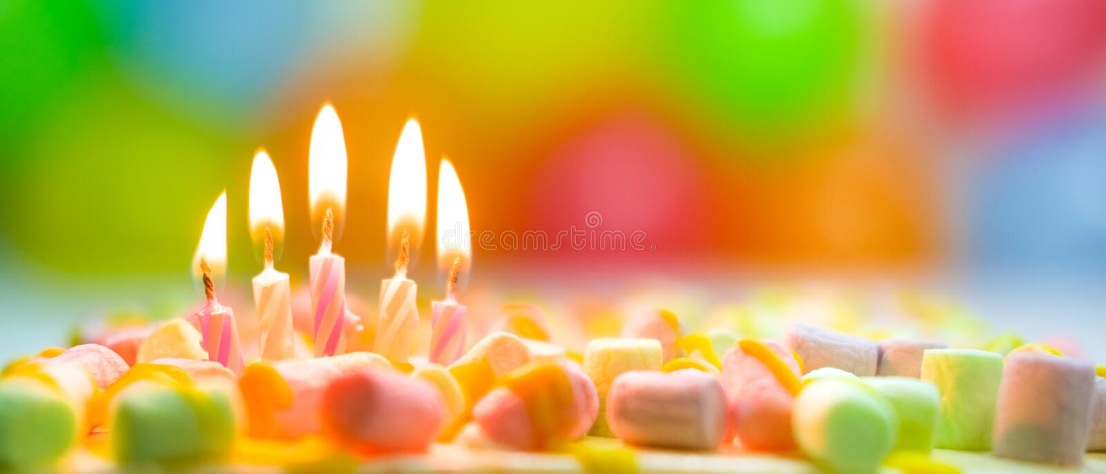 Festive colorful birthday banner with five burning candles on the cake and colorful balloons on background. Space for. Congratulatory text stock photos