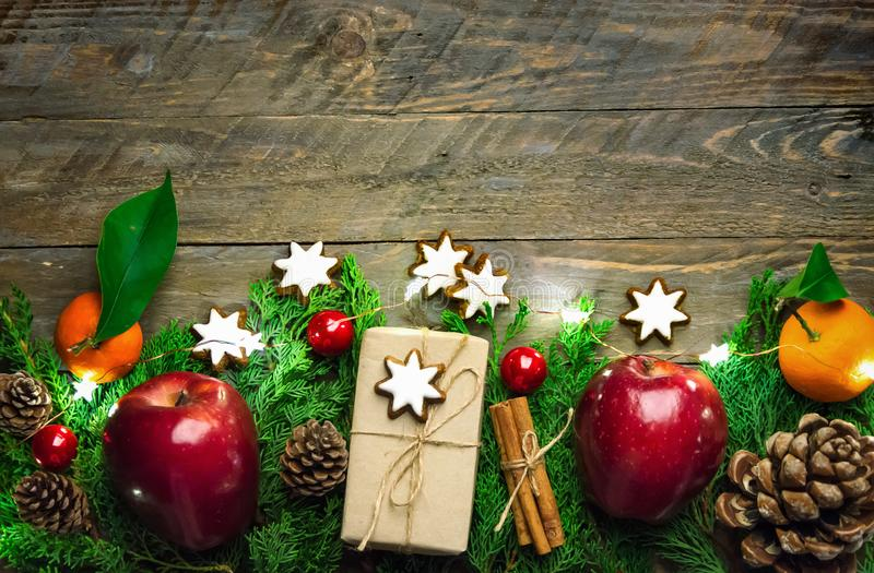 Festive colorful botanical Christmas composition. Fresh green juniper red apples pine cones baubles gift boxes in craft paper stock image