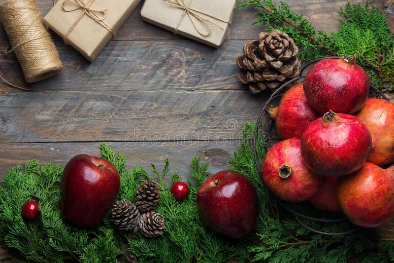 Festive colorful botanical Christmas composition. Fresh green juniper red apples pomegranates pine cones bauble gift boxes wood stock photography