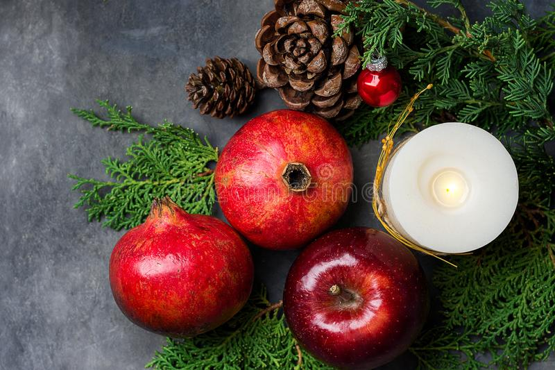 Festive colorful botanical Christmas composition from natural materials. Green juniper red apples pomegranates pine cones candle royalty free stock images