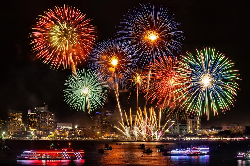 Festive colorful firework light up the sky over the city at nigh royalty free stock photography