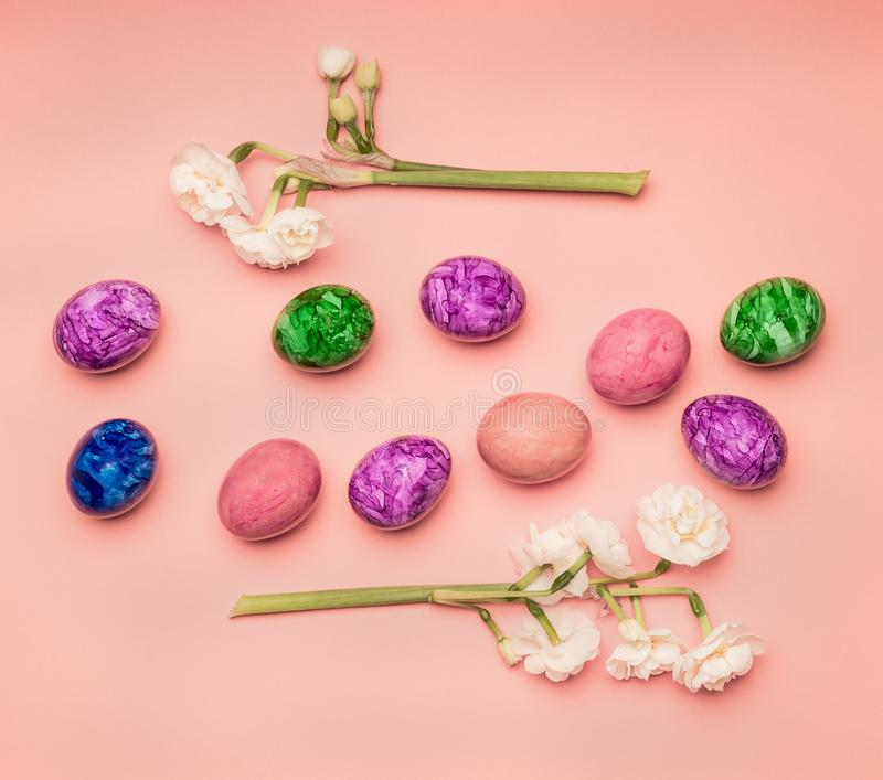 Festive composition, colorful Easter eggs and daffodils on a pink background royalty free stock photography