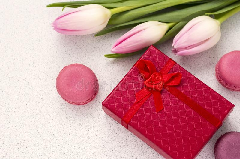 Festive composition, delicate tulips and almond cookies with a red gift box royalty free stock photos