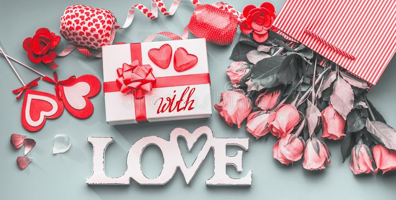 Festive composition of love for Valentines day made with gift box and red bow, shopping bag and roses, hearts and party royalty free stock photography